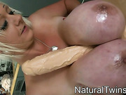 Chubby blonde mommy with big natural juggs in a blue bikini rubbing a toy between them