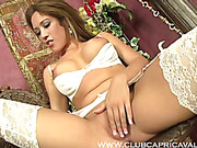 Alluring hottie in all white lingerie spreads her legs wide and rubs her pussy on a brown chair before getting her multi-colored fiber glass dildo and sucks it sensually.