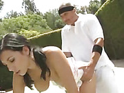 Sweet hottie lets her trainer pull down her white tennis outfit and expose her soft tits before she kneels down and suck his dick then lets him doggy shag her on the court.