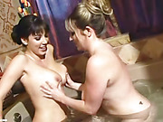 Two hot and naked chicks taking turns mashing each others boobs before they rub their pussies at the same time while bathing together in a tub.