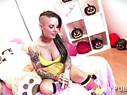 Nasty babe filled with tattoos poses her sexy body before she exposes her hot boobs and rubs her lusty pussy wearing yellow lingerie and colorful socks then she spreads her legs wide on a pink bed and fingers her crack beside a big brown teddy bear.