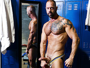 Jock jacks off his junk in front of a mirror in the locker room.