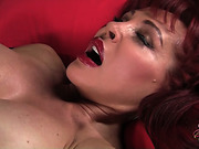 Horny red bombshell in nylons and polka-dot lingerie rubbing her clit with a mini vibro