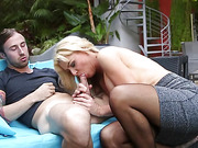 Busty blonde mature in a grey skirt and torn pantyhose serving a younger guy orally at the pool