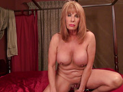 Fair-haired granny with massive boobs pounding her shaved cunt with a wire dildo