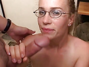 Perky blonde in glasses wraps her mouth around two cocks while on her knees.