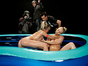 Oiled babes wrestling in a small inflatable pool give a man's shaft a warm welcome.