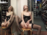 Blonde in black stockings pounds her cunt with a black dildo inside a dressing room.