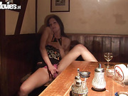 Woman slides fingers into her pink panties while seated in a restaurant booth.