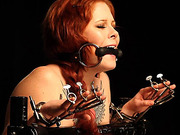 Gagged and bound redhead revels in being completely submissive to another woman.