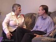 Delightful broad in a white top and black pants chats with a guy on the sofa.