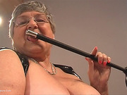 First-rate elderly woman in black leather flogs her pussy in bed.