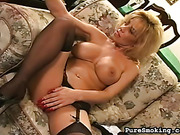 Mature smoker with big tits smokes a cig and pounds her own pussy with a huge dildo.