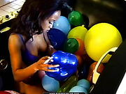 Ebony in a balloon-filled tub plays with the latex spheres while smoking a cig.