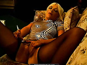 Smoking blonde bombshell in black nylons and a sexy shirt uses her free hand to rub pussy.