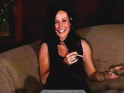 Brunette mom in a black vest looks sexy while smoking in her sitting room