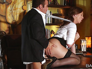 Slutty brunette secretary in office suit and stockings riding her boss' dick right in his desk