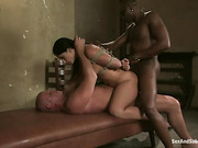 Bound gagged brunette gets a good stuffing for kinky master and his black assistant