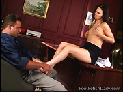 Brunette girl giving cool footjob to her boss in his office