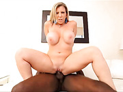 Sweet MILF in multi-colored dress and green high heels kneels down and sucks her black boyfriend's cock before she gets naked and rides on it then lets him doggy fuck her on a white couch.