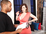 Alluring cougar wearing sexy red dress teases a hot black dude then kneels down and sucks his cock before she gets naked and rides on it then lets him doggy fuck her on a gray couch.