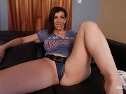 MILF hottie sits on a black couch and takes off her blue shirt and black panty then spreads her legs wide and rubs her pussy.