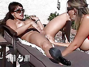 Smoking hot cougar wearing red bikini bra lays prone and displays her sweet butt hole outdoor before she drills a white dildo between a naked luscious babe's pussy on a gray beach bed then they go inside before she sucks a huge black dick then gets fucked