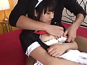 Pretty young Japanese in black and white nurse outfit lets her hunk master slide her hand inside her white lingerie then squeeze her soft tits and rubs her pussy on a red bed.