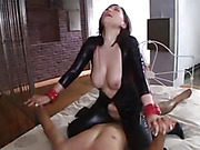 Gorgeous chick with big tits bends over on a white and gray bed then lets him bang her from behind before she rides on his cock wearing her black leather outfit.