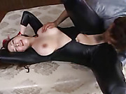 Alluring babe bares her big boobs wearing her tight leather outfit while her hands cuffed in jail before she lays down on a white and gray couch and lets an office lick her hairy pussy.