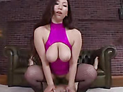 Luscious Japanese babe releases her huge juggs wearing her sexy pink dress and black fishnet stockings before she rides on a hot stud's dick on a white carpet.