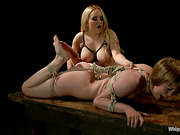 Naughty young lady receives a lesson in absolute submission during a fierce lesdom session.