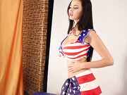 Long haired brunette cutie wrapped in a USA flag shows her boobs