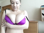 Passionate model with a purple bra rubs her massive natural knockers