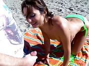 A hot brunette in a skimpy bikini invites a horny voyeur for a closer look at the beach