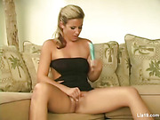 Smoking hot blonde displays her luscious body then opens her legs wide and rubs her juicy twat before she tickles it with a blue vibrator on a brown couch wearing her black dress on a high heels.