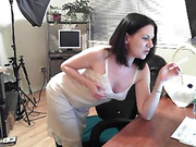 MILF in white dress lifts her legs on the desk to masturbate.