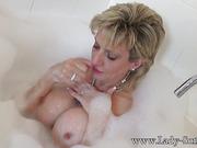 Horny cougar talks dirty while enjoying the bathtub bubbles naked.