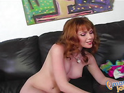 Steaming hot redhead sits naked on a gray couch then bares her sweet tits and hot body while she rubs her indulging pussy before she jacks a huge dick in different positions til she makes it cum on her hand.