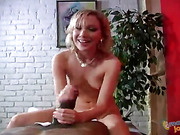 Luscious blonde teases a horny man as she takes off her white shirt and shows him her hot boobs and foxy body before she goes down and jacks his dick wearing her blue panty then makes him blow his spunk on a red couch.