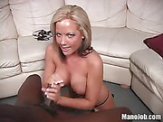 Steaming hot blonde displays her luscious body as she kneels down topless and jacks a huge black cock wearing her black thong til she makes it cum on her alluring boobs.