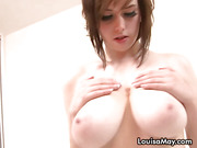 Chick with hazel colored hair and massive tits poses and strips her clothes off