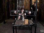 Hot redhead gets cuffed and hanged naked then gets her mouth gagged with a red ball and her boobs squeezed with steele bars before she gets her head and hands locked on wooden cuffs then gets her mouth jackhammered by a flesh dildo her tits sucked and her
