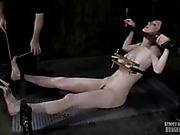 Naked babe gets bent over and bounded on a black chair then gets her lusty ass whipped before she lays down and gets her head, hands and feet cuffed, her tits squeezes with wooden bars and her pussy rubbed by a black vibrator.