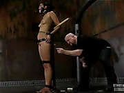 Skinny chick gets cuffed on iron bars then gets her ass whipped before she gets tied on another pole and gets gagged with a red ball before getting spanked with a stick.