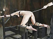 Sexy hottie gets strapped naked on steel pipes with her head locked in a metal sphere then gets electricuted before she gets tied bend over on wooden bars and gets her head wrapped in black mask then lets a fat dude spank her butt with a stick.
