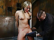 Luscious babe with smoking hot body gets tied naked on a metal post then gets her mouth gagged with a red ball and her juicy tits clipped while getting her sweet pussy vibrated before she gets cuffed on other pipes while she lays down prone then gets elec