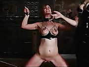 Luscious babe gets her head locked in a steel sphere then lets a tattooed redhead in black dress spank her tits with a stick then pulls down her panty and rubs her twat with a black vibrator before she cuffs her on a metal pole then clips her sweet tits a