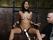 Luscious babe gets cuffed naked on iron pipes then gets her mouth gagged with a red ball and her boobs sucks with suction cups before she bends over and gets her head and hands locked on a wooden bar then lets a big mohawk dude shove a big dildo in her mo