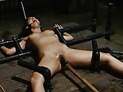 Alluring brunette with sexy body lays prone and naked then gets bounded on a brown bed with her mouth strapped with a red ball before she gets her hot ass electricuted then she gets cuffed on metal pipes then gets her tits clipped and her pussy drilled wi
